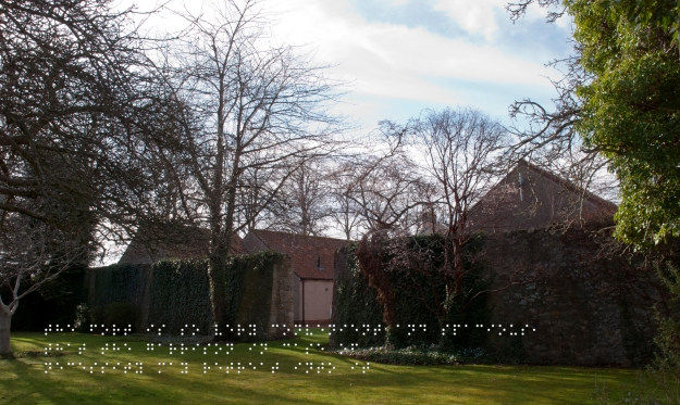 Bailey wall, now separating houses from a green space. Quote taken from historical figure shown in Braille